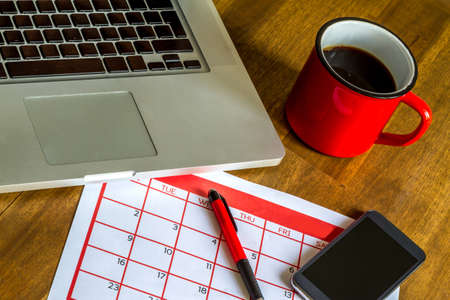 do: Working with the laptop and organizing monthly activities and appointments in the calendar Stock Photo
