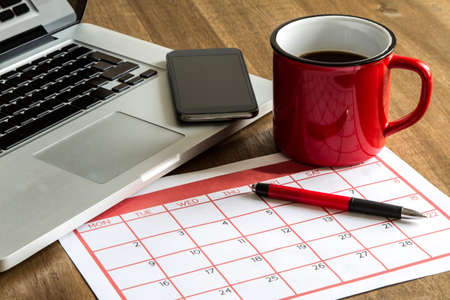 planner: Working with the laptop and organizing monthly activities and appointments in the calendar Stock Photo