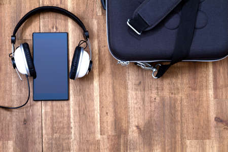 gadget: Cellphone with headphone and a briefcase background Stock Photo