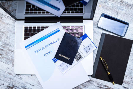travellers: Travel insurance policy booklet with a boarding pass and a passport