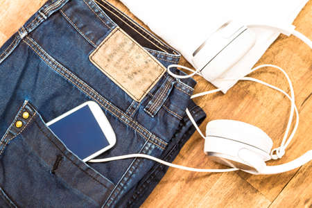informal clothing: Informal male outfit with cellphone and headphone, background