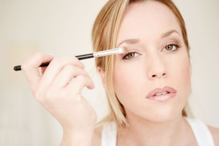 Portait of young beauty woman applying eye shadow photo