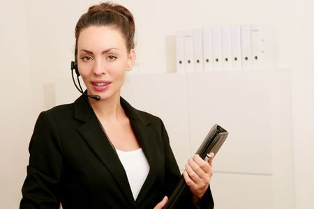 Portrait of beauty young business woman with a headset looking at camera photo
