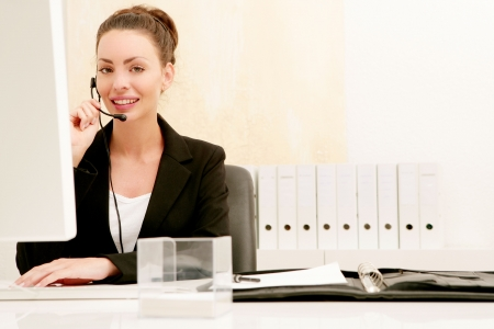 Beauty young woman with a headset phoning in office Stock Photo - 6521295
