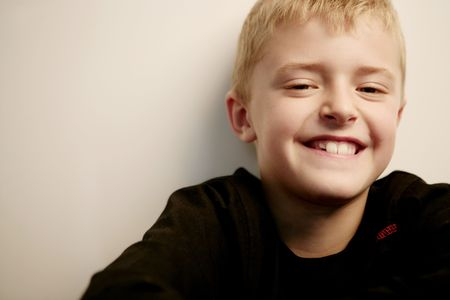 unworried: Close-up of a smiliing blond boy looking at camera