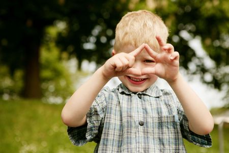 unworried: Small blond boy forming a house with his hands Stock Photo