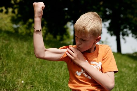 Portrait of a blond boy showing muscles in nature - looking at his bicep