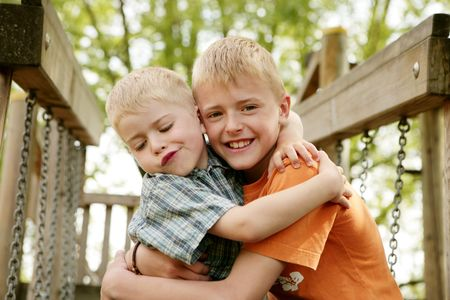 cuteness: Portrait of two smiling boys hugging each other at playground