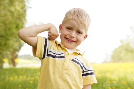 unworried: Portait of a blond small boy showing muscles in nature Stock Photo
