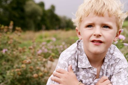 unworried: Close-up face of a small blond cute boy posing in nature