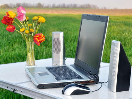 Laptop and audio system on the table in steppes of Ukraine. photo