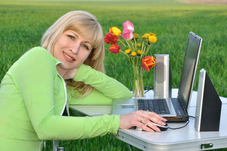 Lady works on a laptop on the nature photo