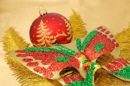 A christmas decoration and carnival mask on a gold branch of a fern photo