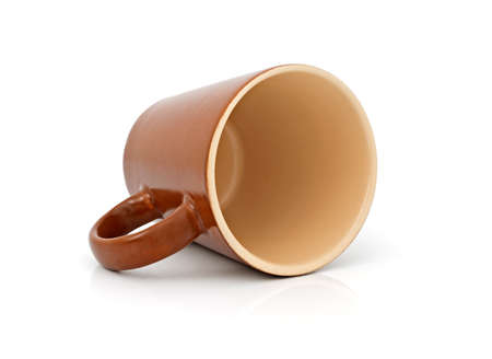 overturn: Overturned ceramic cup on the white background