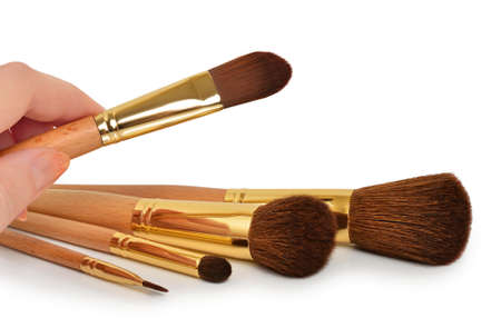 Female hand takes the cosmetic brushes for a powder and eye shadow  Isolated on a white background Stock Photo - 12610557