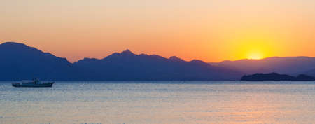 Sea and mountains against the backdrop of the sunset photo
