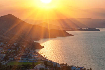 Sunset over a seaside small town against a sea and mountains photo