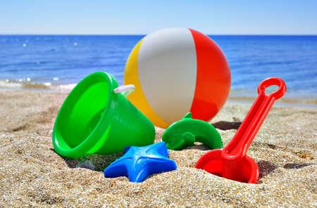 Giocattoli per i bambini s sulla spiaggia contro il blu del mare e del cielo