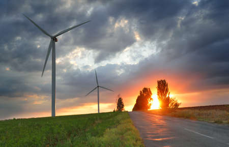 Old road and wind power generators against dramatic sky at the sunset photo