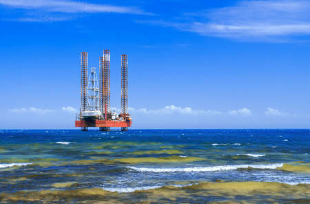 Offshore oil rig drilling platform in the sea against the blue sky