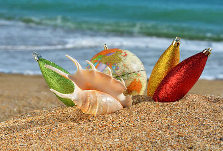 Christmas decorations and seashell on yellow beach sand against ocean wave photo