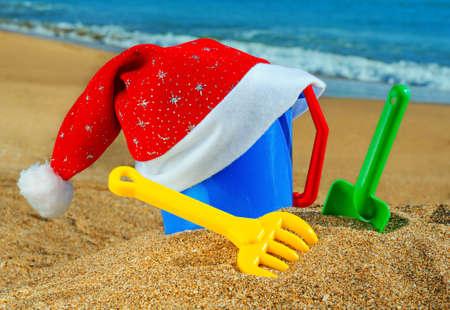 Children's toys and Santa Claus cap on the beach against a blue ocean Stock Photo - 16086595