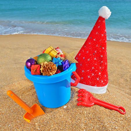 christmas toy: Christmas toys, decorations and Santa Claus cap on the beach against a blue ocean Stock Photo