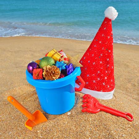Christmas toys, decorations and Santa Claus cap on the beach against a blue ocean Standard-Bild