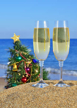Glasses of champagne and Christmas tree on the beach against the blue sea photo