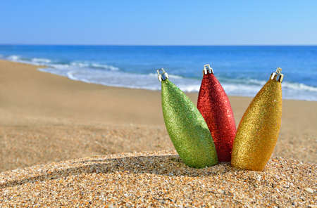 Christmas decorations on yellow beach sand against blue ocean photo