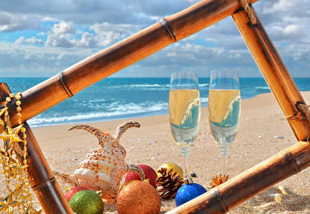 christmas bubbles: Christmas seascape in bamboo frame on the beach whis Christmas decorations and glasses