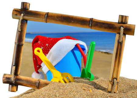 children's: Children s toys and Santa s hat  in bamboo frame on the beach against a blue ocean isolated on white background