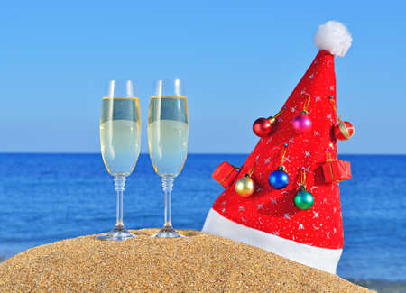 Glasses of champagne and Santas hat adorned with Christmas decorations on the beach sand.