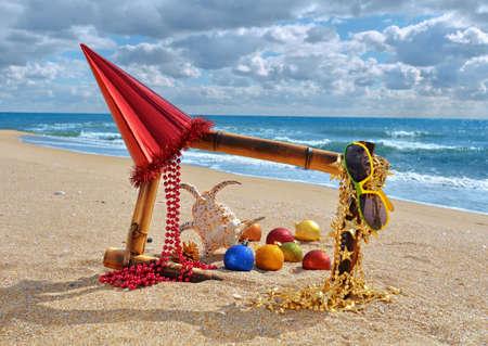 Bamboo frame with Christmas decorations on the beach against blue sea and cloudy sky. Christmas seascape.  Standard-Bild