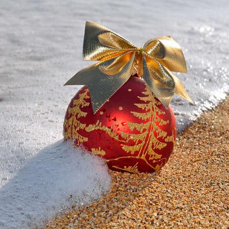 Christmas decoration on yellow beach sand against ocean wave