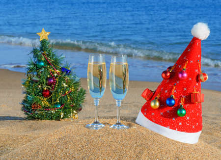 Glasses of champagne, Christmas tree and Santa's hat on the beach against a blue sea