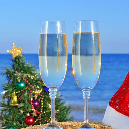 Glasses of champagne and Christmas tree on the beach against a blue sea