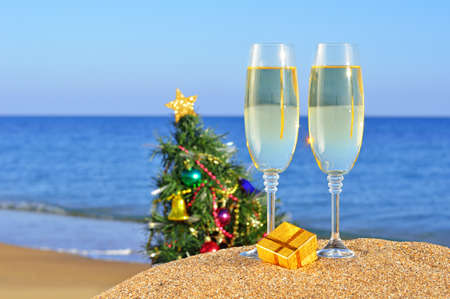 Glasses of champagne and Christmas tree on the beach against the blue ocean photo