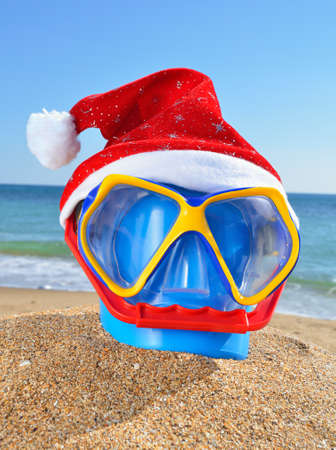 Baby bucket, diving mask and Santas hat on the beach against a blue sea photo