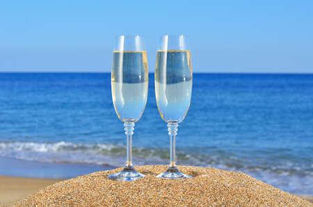 Copas de champán en la arena de la playa Foto de archivo