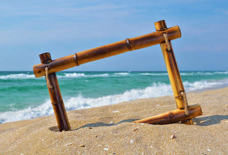 new years vacation: Seascape with bamboo frame on the beach sand against turquoise sea and blue sky Stock Photo