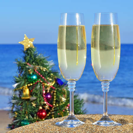 Seascape with glasses of champagne and Christmas tree on the beach against the blue sea and sky photo