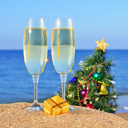 Glasses of champagne and decorated Christmas tree on the beach against the sky and blue sea photo