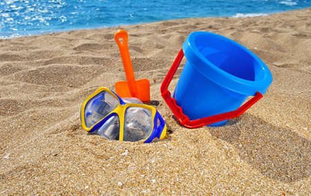 gold shovel: Baby bucket, shovel  and diving mask on the beach against the azure sea