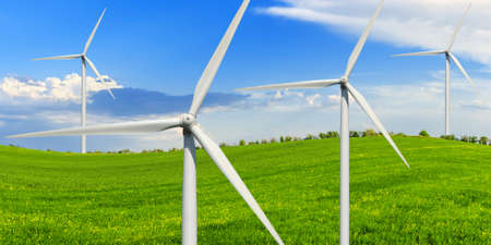alternative energy sources: Spring sunny day on a green meadow with wind power generators.