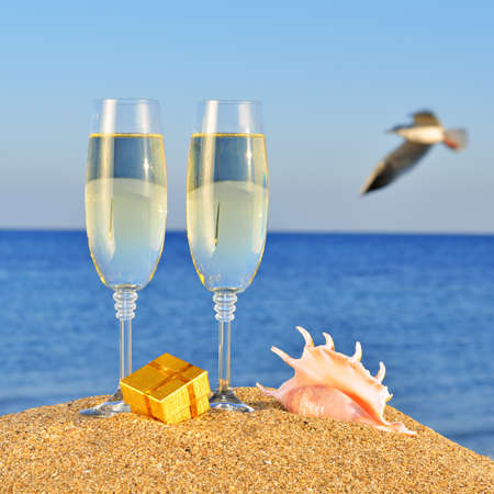 Glasses of champagne, box with a gift  and seashell on the beach against the sky and blue sea photo