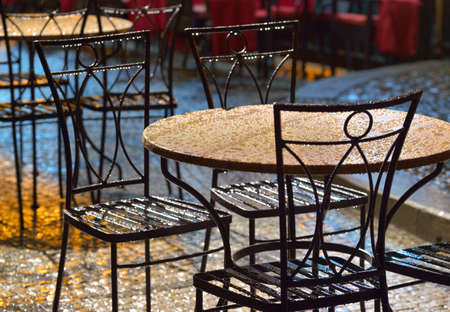backlighting: Tables at an outdoor cafe in the rain, illuminated bright backlighting  Prague   Stock Photo
