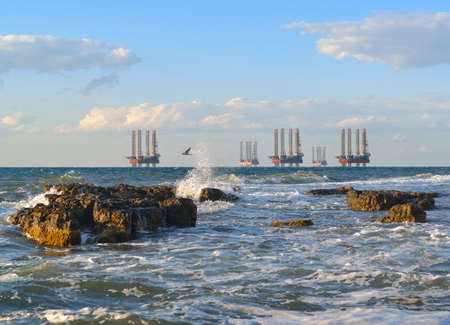 boring frame: Sea station of gas production  Drilling platforms in the sea at sunset against a blue sky Stock Photo