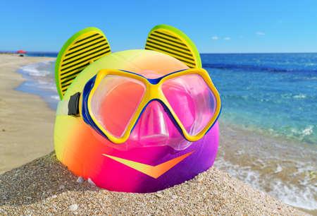 the little man: Sorridente uomo di accessori da spiaggia palla, flip-flop e maschera sulla spiaggia contro un mare blu e il cielo