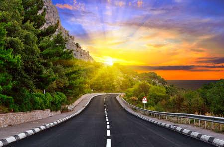 Highway tegen bergen en een dramatische zonsondergang